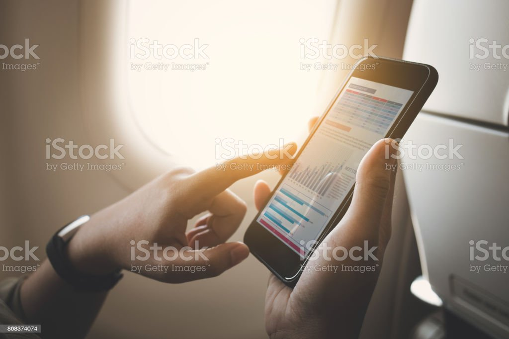 Businesswoman on plane using smartphone with graph on screen stock photo