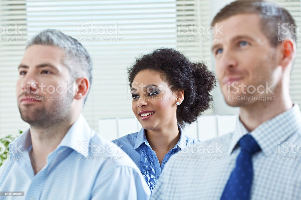 Businesswoman on seminar Three business people during business conference. Focus on smiling businesswoman sitting in second row. 25-29 Years Stock Photo