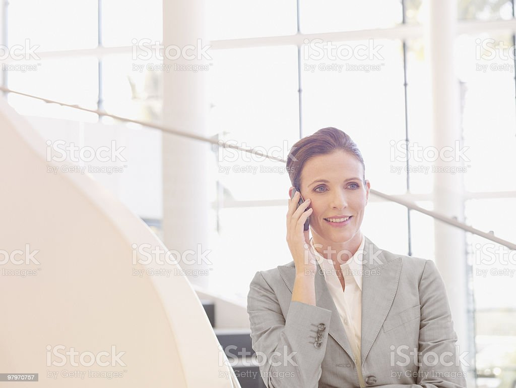 Businesswoman on stairs talking on cell phone royalty-free stock photo
