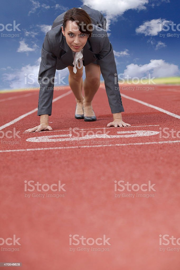 Businesswoman on start line of a running track stock photo