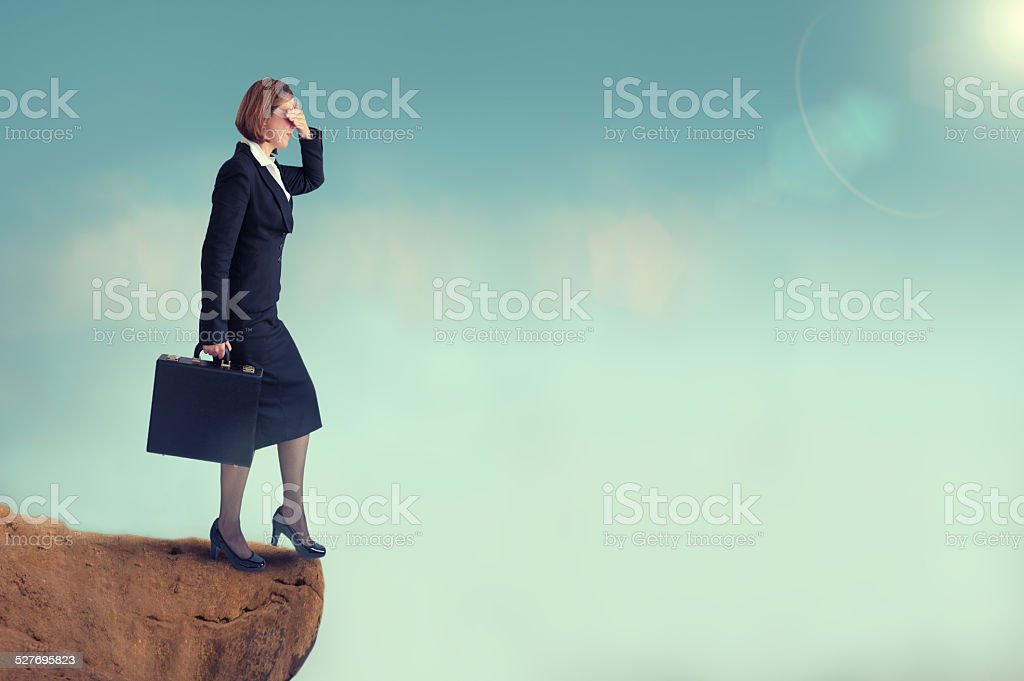 businesswoman on the edge of a cliff stock photo