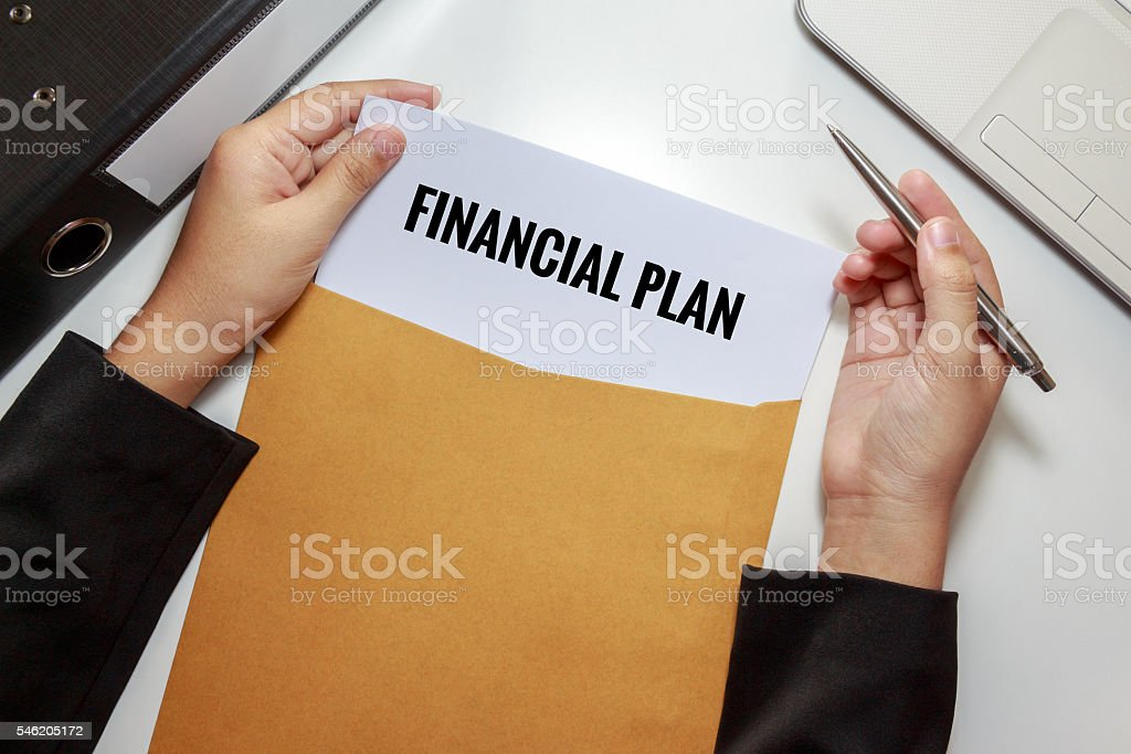 Businesswoman opening Financial Plan document in letter envelope stock photo