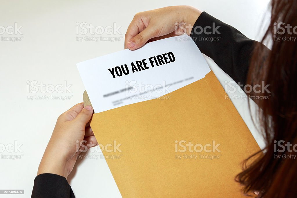 Businesswoman opening the Fired document in letter envelope stock photo