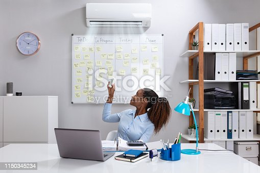 istock Businesswoman Operating Air Conditioner In Office 1150345234