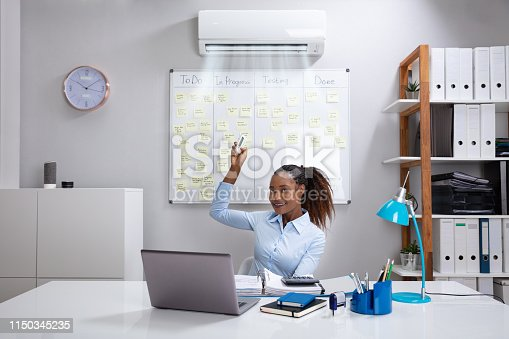 istock Businesswoman Operating Air Conditioner In Office 1150345235