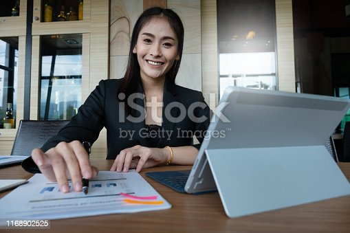 istock Businesswoman or accountant hand holding pen and pointing at financial paperwork with financial document. 1168902525