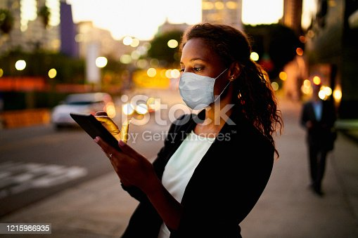 Businesswoman using a digital tablet at night in the city wearing a healthcare mask.