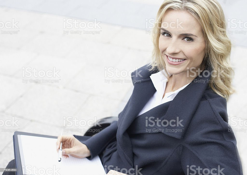 Businesswoman outdoors writing in notebook royalty-free stock photo
