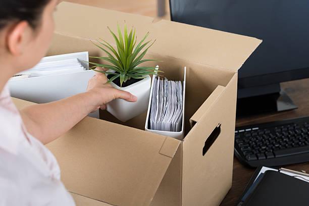 geschäftsfrau verstauen sie ihre habseligkeiten in cardboard box - ausscheiden stock-fotos und bilder