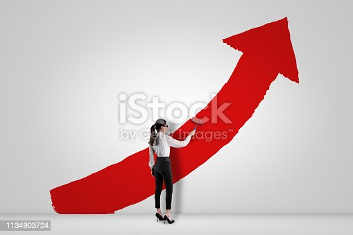 959023366istockphoto Businesswoman painting red arrow sign painting on white wall 1134903724