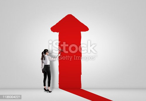 959023366istockphoto Businesswoman painting red arrow sign painting on white wall 1135004221