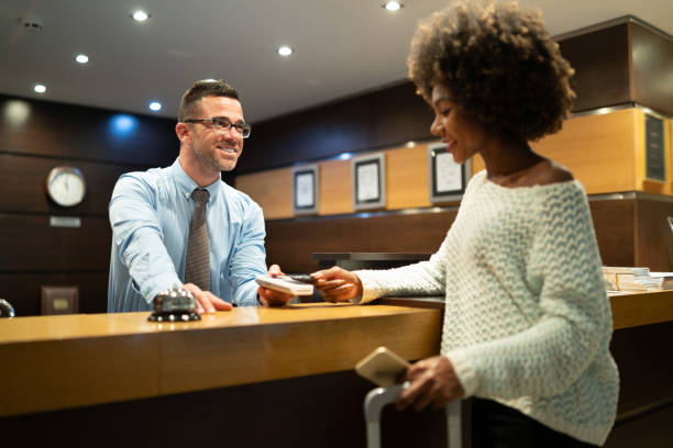 Businesswoman paying at hotel reception Businesswoman at reception, paying for hotel room. concierge stock pictures, royalty-free photos & images