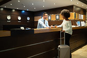 Businesswoman at reception, paying for hotel room.