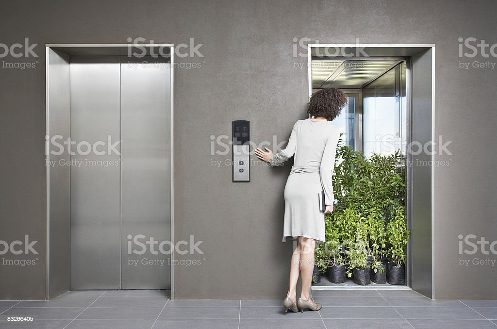 Businesswoman peering at elevator full of plants royalty-free stock photo