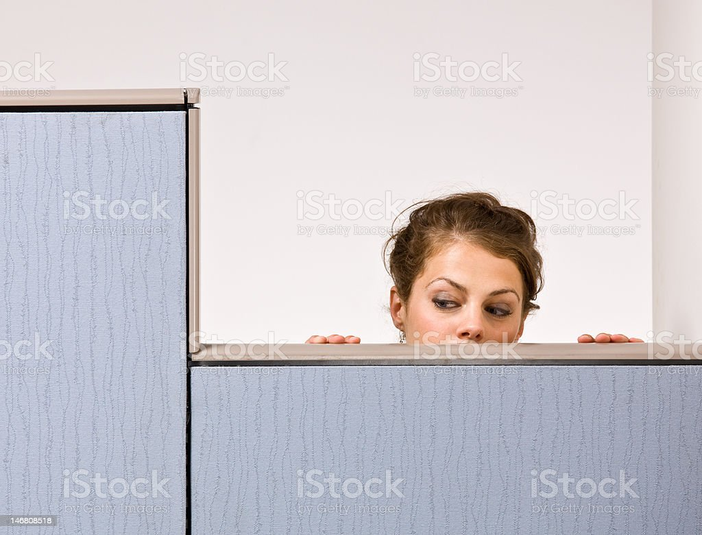 Businesswoman peering over cubicle wall stock photo