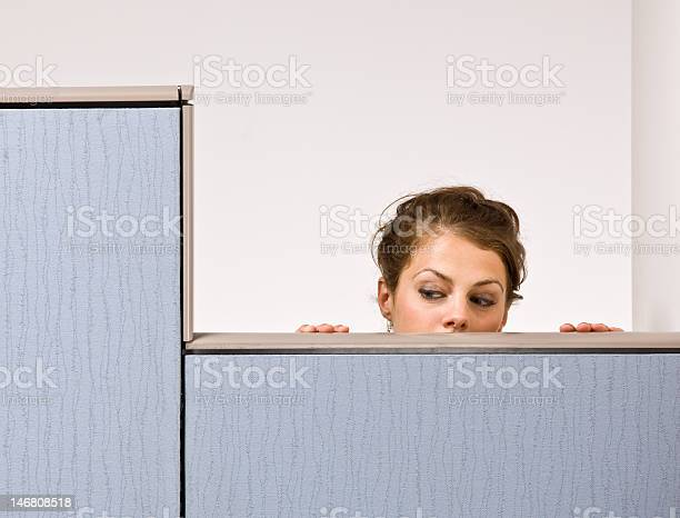 Businesswoman Peering Over Cubicle Wall Stock Photo - Download Image Now