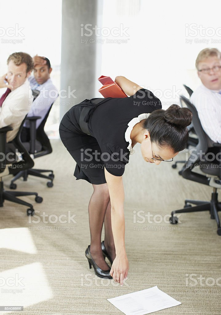 Businesswoman picking papers up from floor stock photo