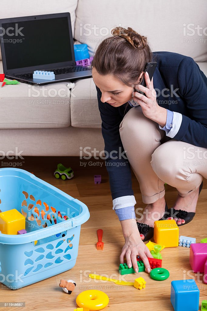 Businesswoman picking up toys stock photo