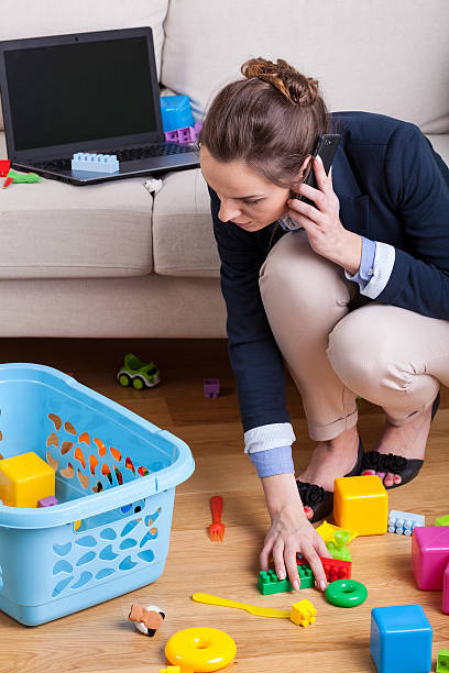Businesswoman picking up toys Businesswoman talking on phone and picking up toys kids cleaning up toys stock pictures, royalty-free photos & images