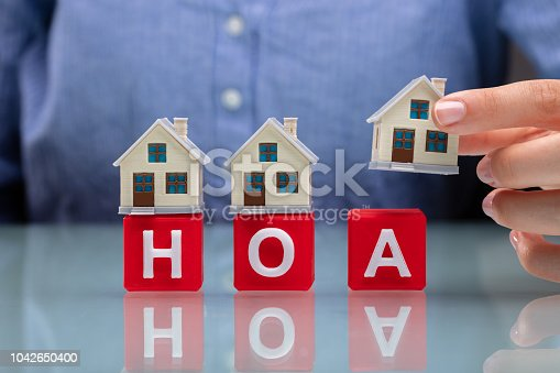 istock Businesswoman Placing House Models On HOA Cubic Blocks 1042650400