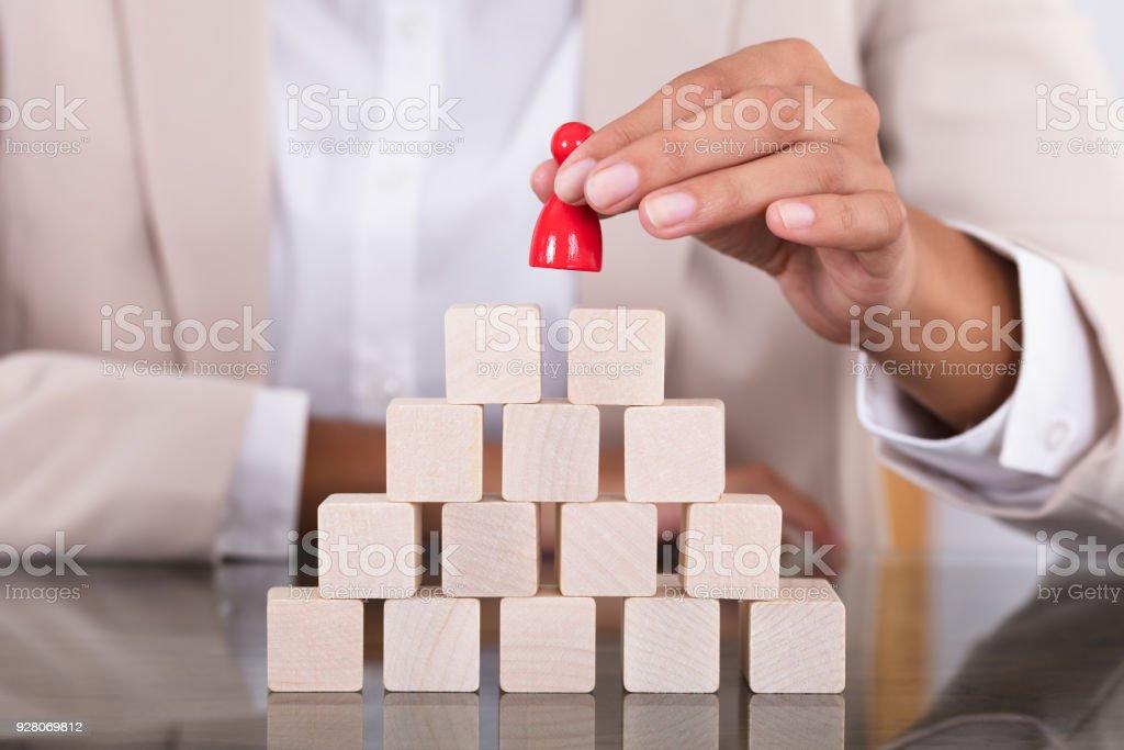 Businesswoman Placing Red Figure On Arranged Blocks stock photo