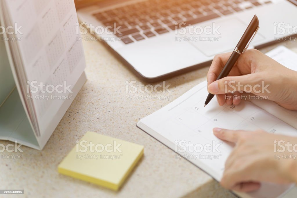 Businesswoman planning agenda and schedule using calendar event planner. Woman hands writing plan on notebook. Calender planner organization management remind concept stock photo