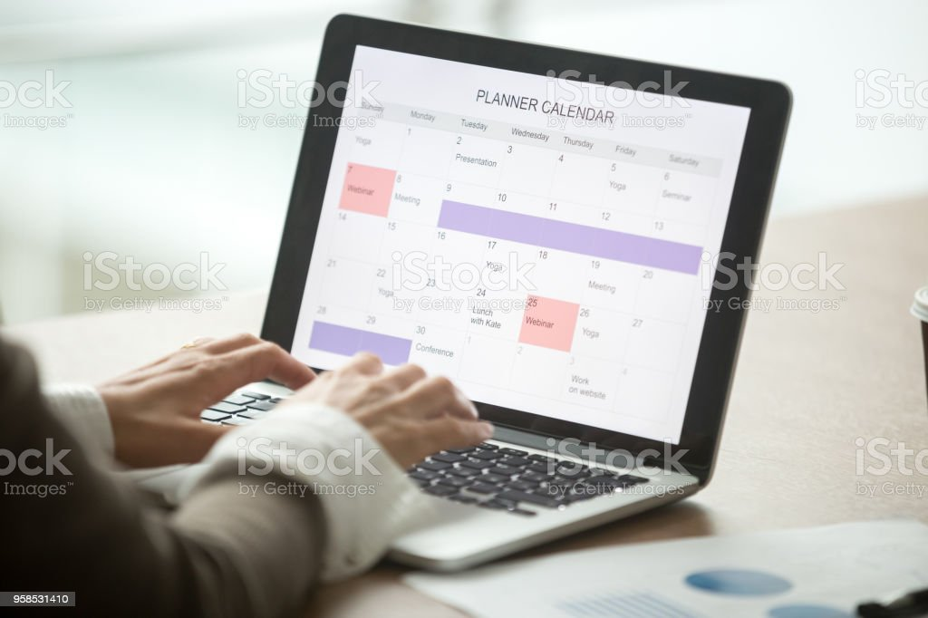Businesswoman planning day using digital calendar on laptop, closeup view stock photo