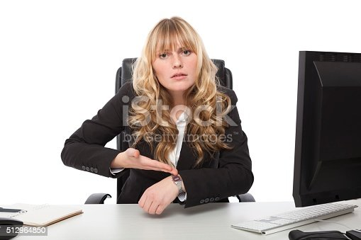 Businesswoman pointing at her wrist watch with her hand and an intense look on her face as she tries to explain something