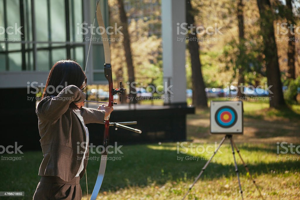 Businesswoman Pointing The Target With Bow And Arrow stock photo