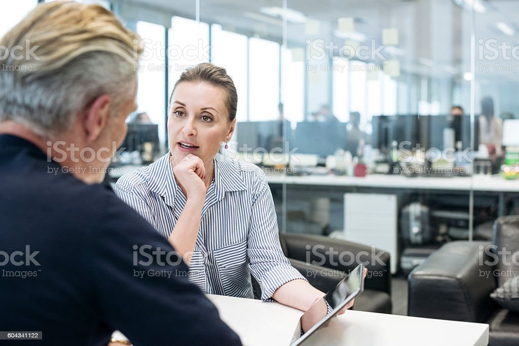 Businesswoman pointing to tablet and explaining to male colleague stock photo