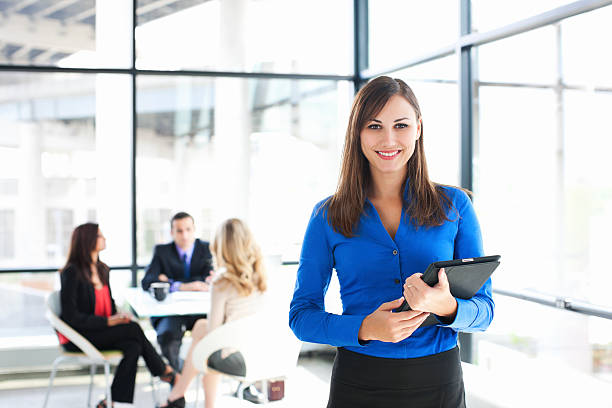 Businesswoman Portrait with Coworkers Meeting in Background, Copy Space stock photo