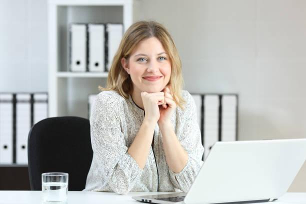 zakenvrouw poseren op zoek naar jou op kantoor - jonge vrouw stockfoto's en -beelden