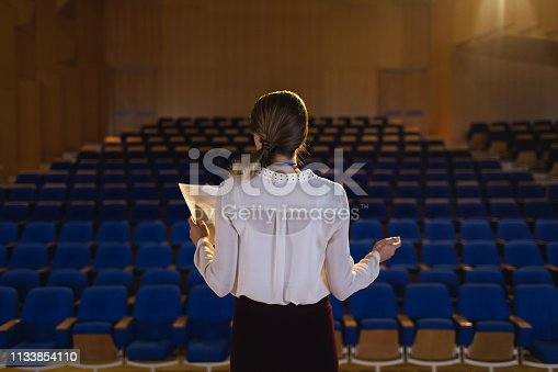 1133973551 istock photo Businesswoman practicing and learning script while standing in the auditorium 1133854110