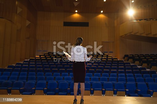 1133973551 istock photo Businesswoman practicing and learning script while standing in the auditorium 1133854239