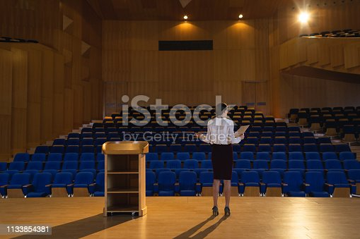 1133973551 istock photo Businesswoman practicing and learning script while standing in the auditorium 1133854381