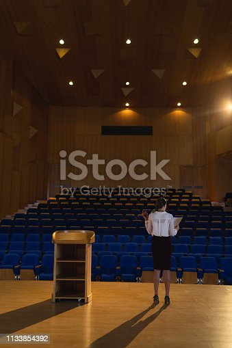 1133973551 istock photo Businesswoman practicing and learning script while standing in the auditorium 1133854392