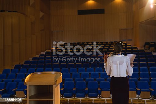 1133973551 istock photo Businesswoman practicing and learning script while standing in the auditorium 1133854408