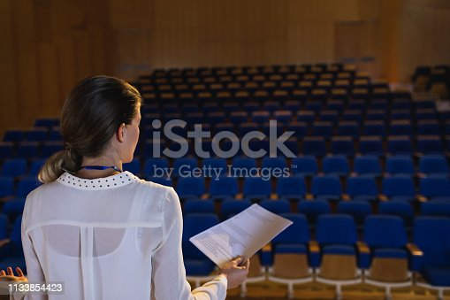 1133973551 istock photo Businesswoman practicing and learning script while standing in the auditorium 1133854423