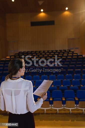 1133973551 istock photo Businesswoman practicing and learning script while standing in the auditorium 1133854442