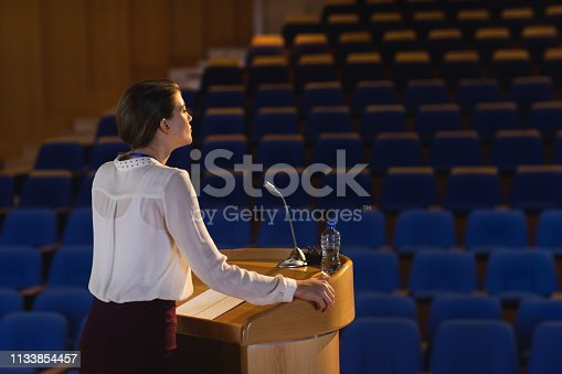 1133856033 istock photo Businesswoman practicing for speech in the empty auditorium 1133854457