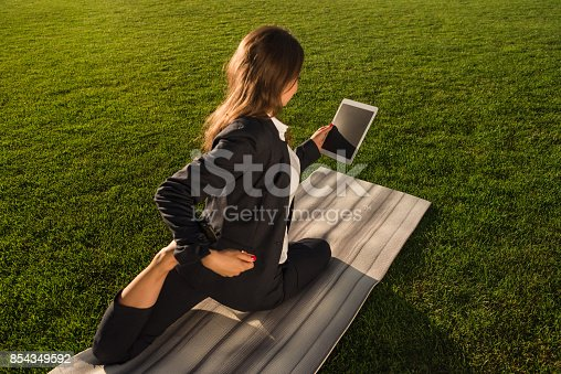 istock businesswoman practicing yoga with tablet 854349592