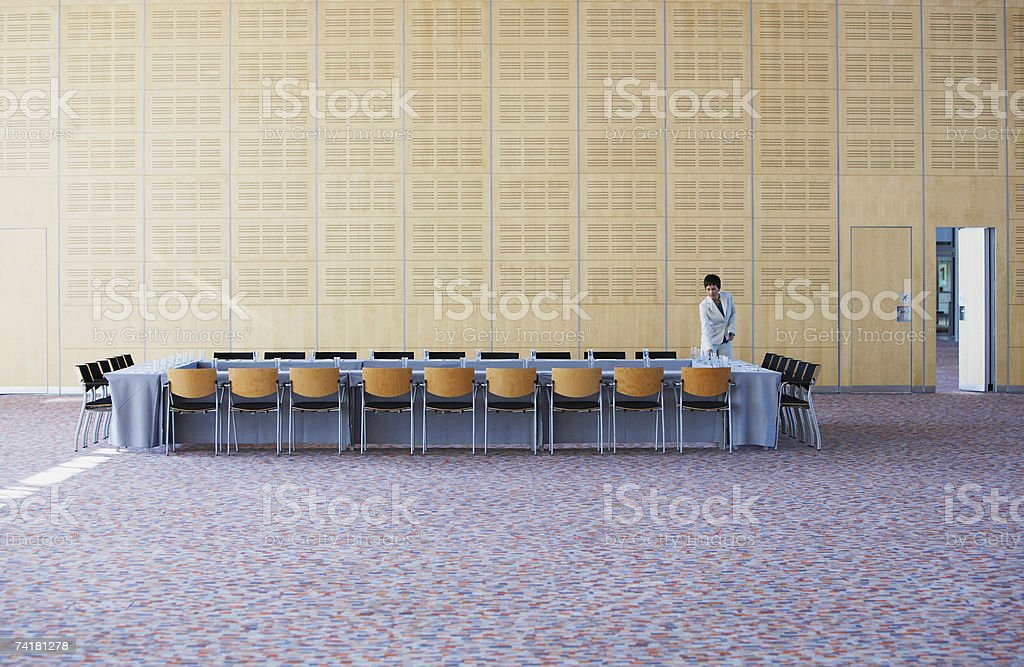 Businesswoman preparing meeting room and table stock photo