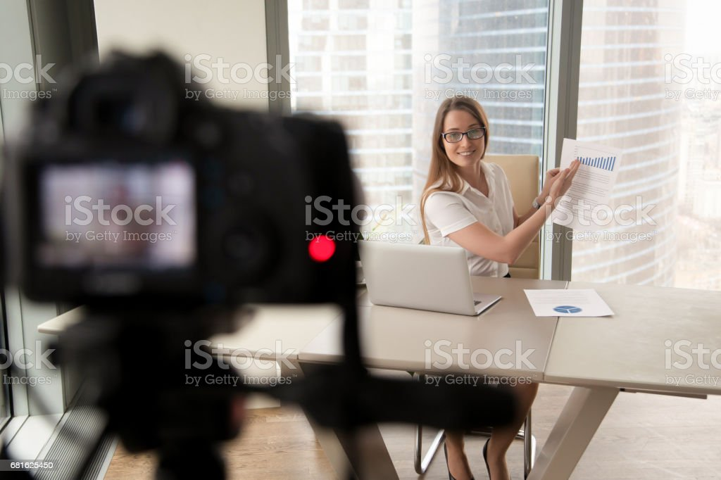 Businesswoman presenting financial stats on camera stock photo