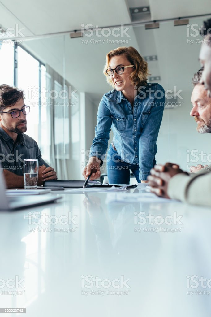 Businesswoman presenting her ideas to coworkers stock photo