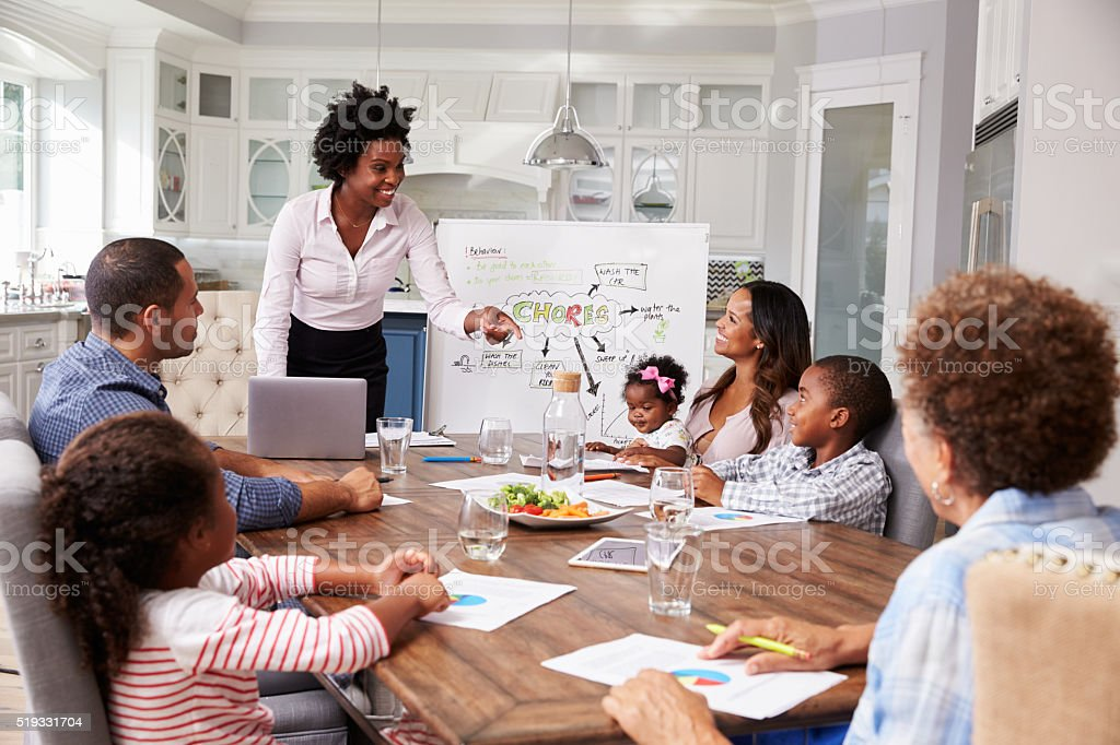 Businesswoman presents meeting to a family in their kitchen stock photo