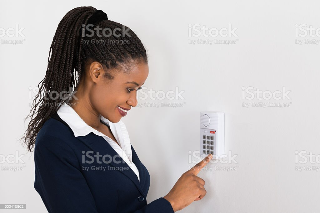 Businesswoman Pressing Button On Security System stock photo