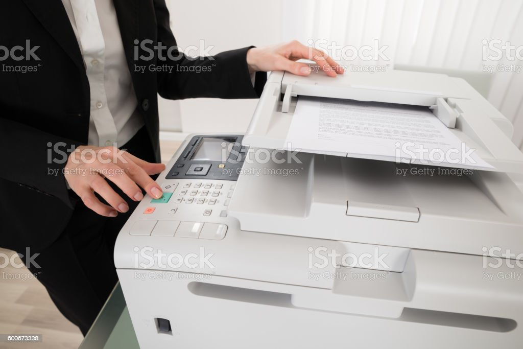 Businesswoman Pressing Printer's Button stock photo