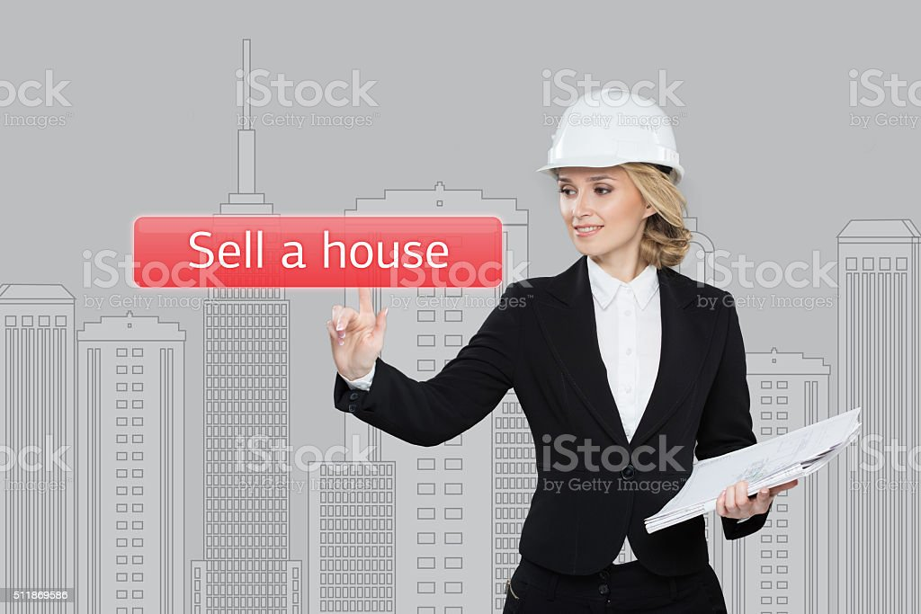 Businesswoman pressing sell a hause button on virtual screens stock photo