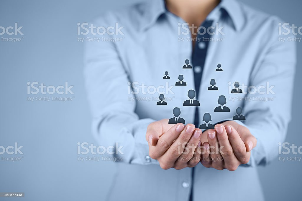 Businesswoman protecting icons of people stock photo