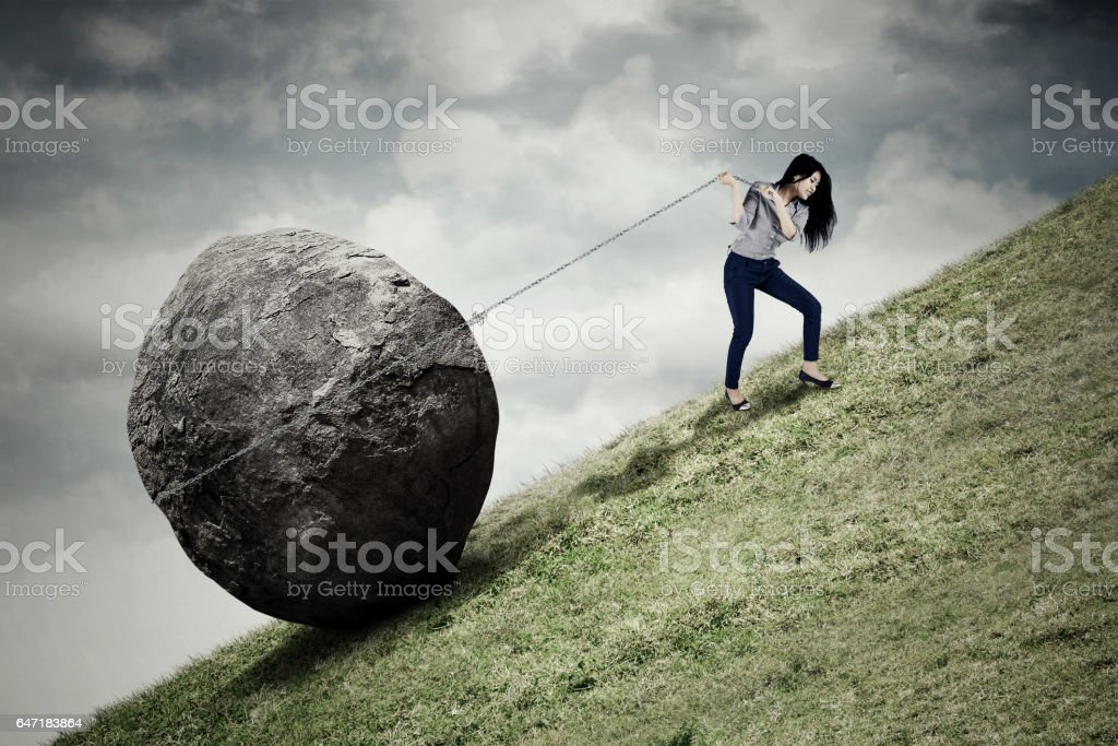 Businesswoman pulling stone on the hill stock photo